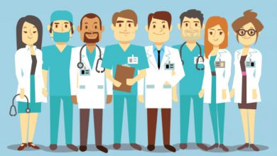 doctors, nurse and pharmacist standing in front of blue wall